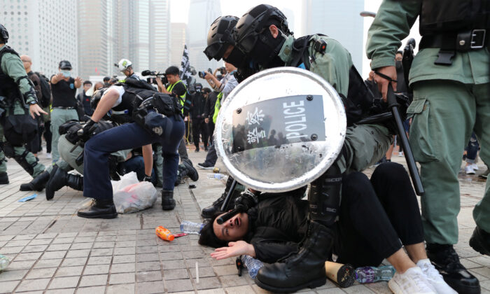 Police arrest a Hong Kong protester after a Chinese flag was removed from a flag pole at a rally in support of Xinjiang Uyghurs' human rights in Hong Kong, China on Dec. 22, 2019. (Lucy Nicholson/Reuters)