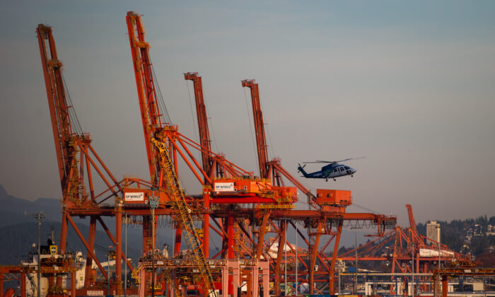 A  helicopter flies past gantry cranes and cargo containers at a Port Metro Vancouver facility on Nov. 2, 2019. Canadian exports have been vulnerable to swings in trade tensions between the United States and China during 2019. (The Canadian Press/Darryl Dyck)