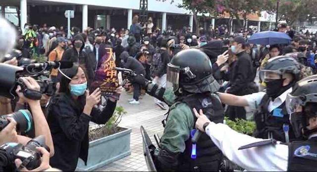 Policejní důstojník míří pistolí na protestující během shromáždění v Hongkongu 22. prosince 2019, zatímco se jej kolegové evidentně pokoušejí strhnout, aby nestřílel. (Anthony Wallace / AFP / Getty Images)