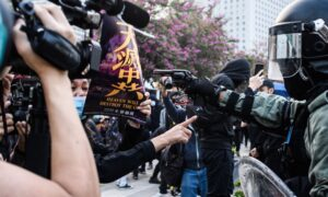 Facing the Barrel of a Gun, Woman Holds Epoch Times Poster to Protest Hong Kong Police