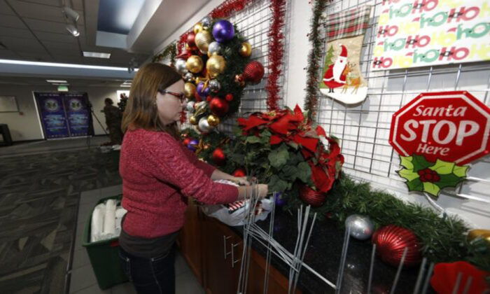 Volunteer Nicole Schreiner places a display of poinsettias in the NORAD Tracks Santa Center at Peterson Air Force Base, in Colorado Springs, Colo.,on Dec. 23, 2019.(David Zalubowski/AP)