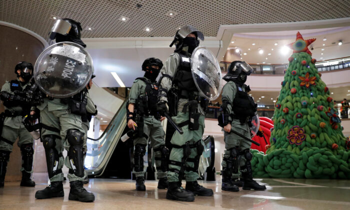 Riot police stand guard next to a Christmas tree inside a shopping mall during a pro-democracy protest on Christmas Eve at Tsim Sha Tsui in Hong Kong, China on Dec. 24, 2019. (Tyrone Siu/Reuters)