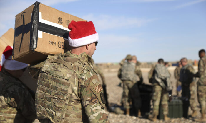 A U.S. soldier carries Christmas gifts from a helicopter to deliver to his comrades on a base near the al-Omar oilfield in eastern Syria, on Dec. 23, 2019. (Farid Abdul-Wahid/AP Photo)