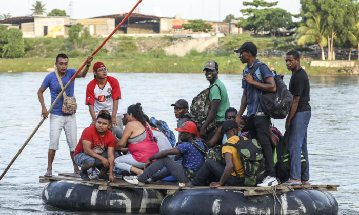 A group of 10 Haitians illegally cross the Suchiate River on a tube raft from Tecun Uman, Guatemala, to Hidalgo City, Mexico, on June 28, 2019. They are bound for the United States. (Charlotte Cuthbertson/The Epoch Times)