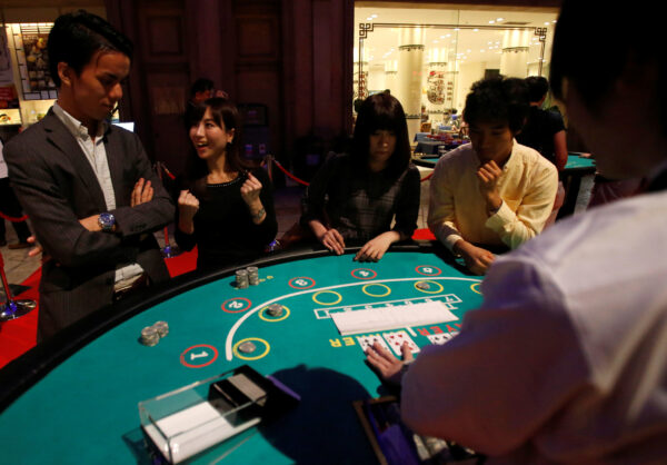 Visitors react after they win a mock baccarat casino game at an international tourism promotion symposium in Tokyo