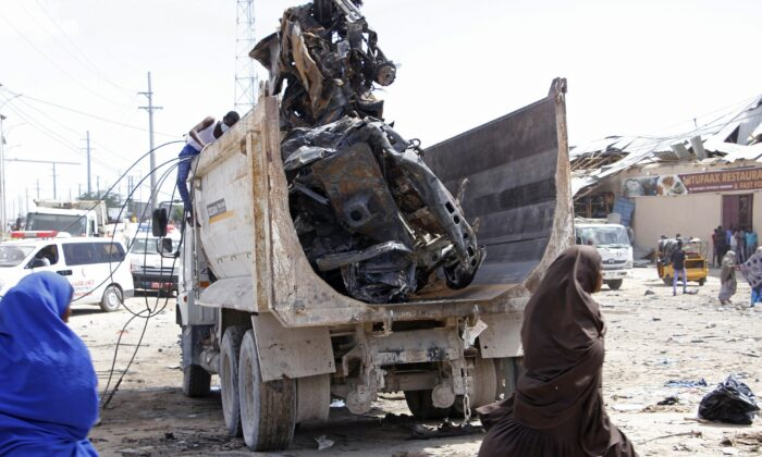 Somali security assess the scene of a car bomb explosion at a checkpoint in Mogadishu, Somalia on Dec. 28, 2019. (Feisal Omar/Reuters)