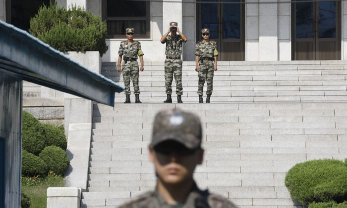 North Korean soldiers (top) look toward the South as a South Korean soldier (bottom) stands guard at the truce village of Panmunjom inside the Demilitarized Zone (DMZ) separating the two Koreas on Aug. 28, 2019. (KIM HONG-JI/AFP via Getty Images)