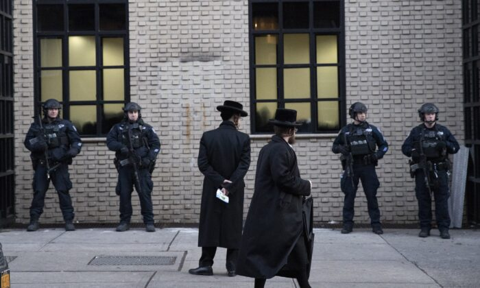 Orthodox Jewish men pass New York City police guarding a Brooklyn synagogue prior to a funeral for Mosche Deutsch in New York on Dec. 11, 2019. (Mark Lennihan/AP Photo)
