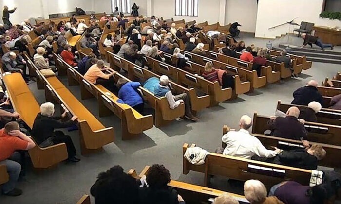 In this still frame from livestreamed video provided by law enforcement, churchgoers take cover while a congregant armed with a handgun, top left, engages a man who opened fire, near top center just right of windows, during a service at West Freeway Church of Christ in White Settlement, Texas, on Dec. 29, 2019. (West Freeway Church of Christ/Courtesy of Law Enforcement via AP)