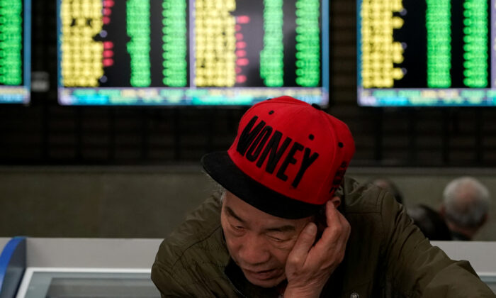 An investor looks at computer screens showing stock information at a brokerage house in Shanghai, China on May 6, 2019. (Aly Song/Reuters)