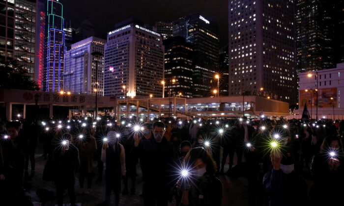 Pro-democracy protesters use the flashlights of their mobile phones as they take part in a protest in Edinburgh Place in Hong Kong, China on Dec. 30, 2019. (Navesh Chitrakar/Reuters)