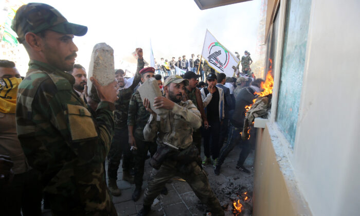 Members of the Hashed al-Shaabi, a group trained and armed by Iran, smash the bullet-proof glass of the U.S. embassy's windows in Baghdad with blocks of cement after breaching the outer wall of the diplomatic mission on Dec. 31, 2019. (Ahmad Al-Rubaye/AFP via Getty Images)