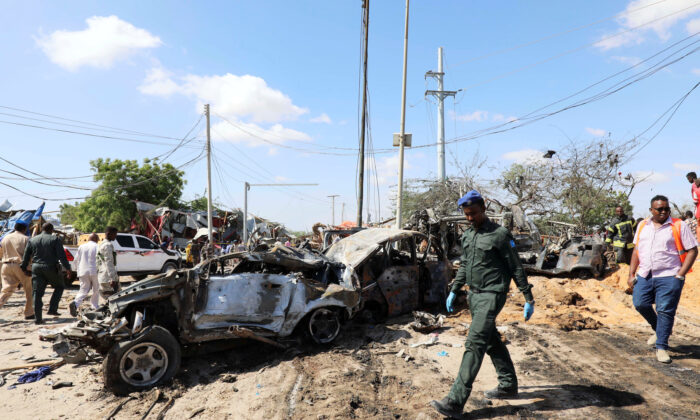 A Somali police officer walks past a wreckage at the scene of a car bomb explosion at a checkpoint in Mogadishu, Somalia  on Dec. 28, 2019. (Reuters/Feisal Omar)