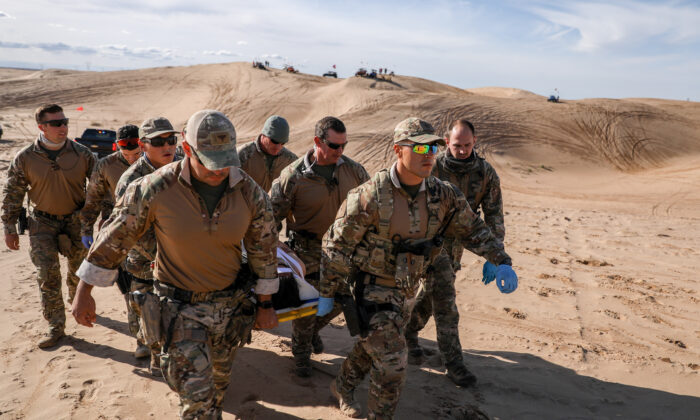 Border Patrol BORSTAR agents carry an injured patient on a stretcher to a waiting helicopter in the Imperial Sand Dunes near the U.S.-Mexico border, Calif., on Nov. 30, 2019. (Charlotte Cuthbertson/The Epoch Times)