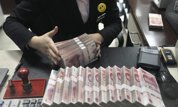 A clerk arranges bundles of 100 Chinese yuan banknotes at a branch of China Merchants Bank in Hefei, Anhui Province, China on March 17, 2014. (Reuters)