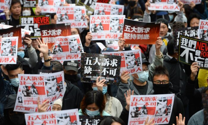 """Protesters hold up placards with the words """"Five Demands, Not One Less"""" in a march in Hong Kong on Jan. 1, 2020. (Sung Pi-lung/The Epoch Times)"""