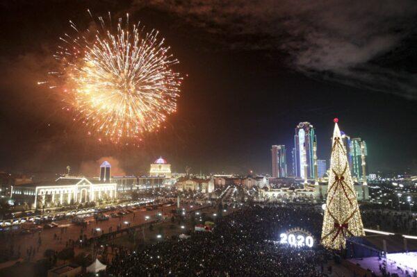 Fireworks explode over a Christmas tree