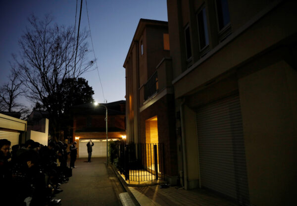 Journalist stand outside the Tokyo residence of former Nissan chairman Carlos Ghosn, while prosecutors raid the house, in Tokyo
