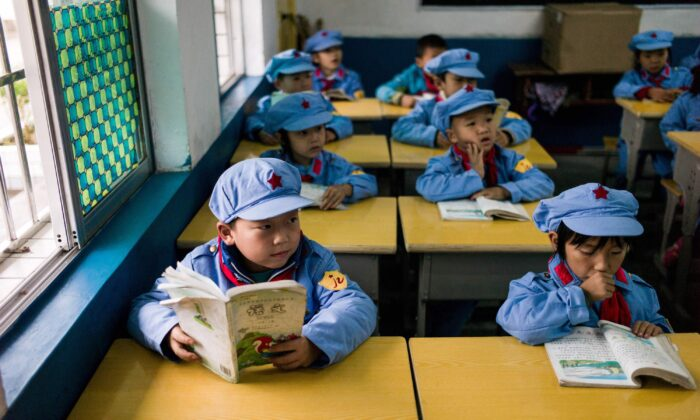 "Students read in their classroom in the Yang Dezhi ""Red Army"" elementary school in Wenshui, Xishui County in Guizhou Province, China on Nov. 7, 2016. In 2008, Yang Dezhi was designated a ""Red Army primary school""—funded by China's ""red nobility"" of revolution-era Communist commanders and their families, one of many such institutions that have been established across the country. Such schools are an extreme example of the ""patriotic education"" which China's ruling Communist party promotes to boost its legitimacy—but which critics condemn as little more than brainwashing. (Fred Dufour/AFP via Getty Images)"