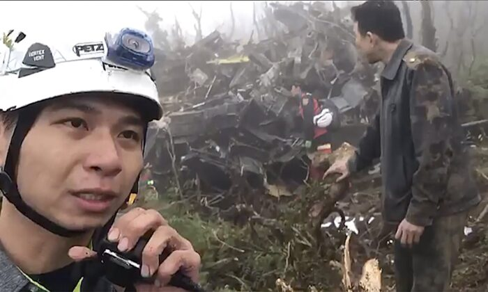 In this image made from video, emergency teams work at the crash site of a military helicopter in the mountains of Yilan, north eastern Taiwan on Jan. 2, 2020. (Yilan Fire Bureau via AP)