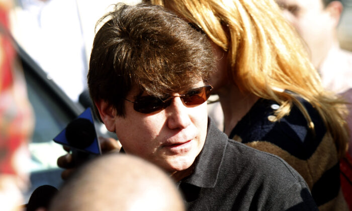Convicted former Illinois Governor Rod Blagojevich walks through a hoard of media toward his house before giving a news conference outside his home in Chicago on March 14, 2012. (Frank Polich/Getty Images)