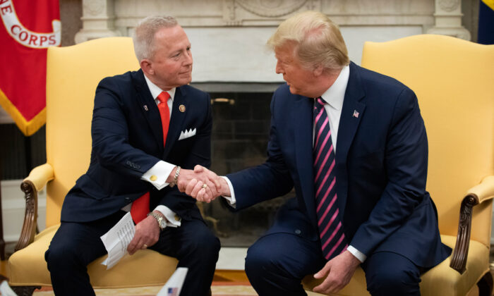 (L-R) Rep. Jeff Van Drew of New Jersey, who has announced he is switching from the Democratic to Republican Party, shakes hands with President Donald Trump in the Oval Office of the White House on Dec. 19, 2019  (Drew Angerer/Getty Images)