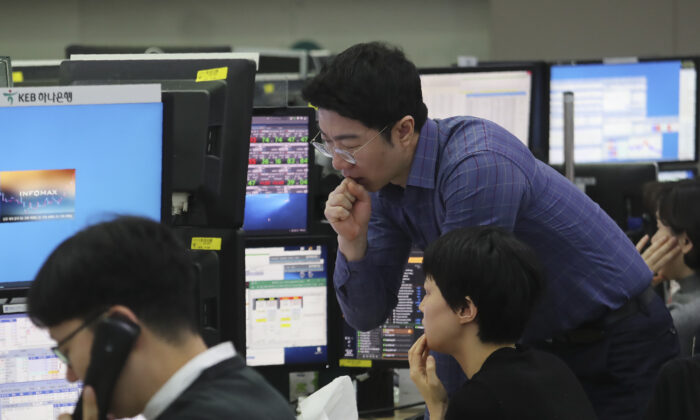 Currency traders watch monitors at the foreign exchange dealing room of the KEB Hana Bank headquarters in Seoul, South Korea, Friday, Jan. 3, 2020. Asian stocks were mixed Friday and oil prices surged after an Iranian general was killed by U.S. forces in Iraq. (Ahn Young-joon/AP)
