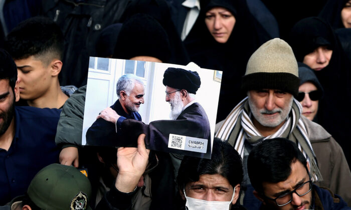 A demonstrator holds a picture of Supreme Leader Ayatollah Ali Khamenei with Iranian Major-General Qassem Soleimani, during protest against the killing of Soleimani, head of the elite Quds Force, and Iraqi militia commander Abu Mahdi al-Muhandis who were killed in an air strike in Baghdad airport, in Tehran, Iran on Jan. 3, 2020. (WANA/Nazanin Tabatabaee via Reuters)