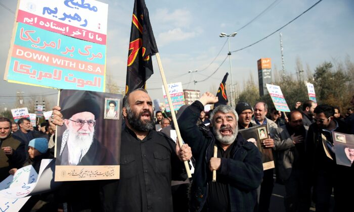 Demonstrators react during a protest against the killing of the Iranian Major-General Qassem Soleimani, head of the elite Quds Force, and Iraqi militia commander Abu Mahdi al-Muhandis who were killed in an air strike in Baghdad airport, in Tehran, Iran on Jan. 3, 2020. (Nazanin Tabatabaee/West Asia News Agency/Reuters)