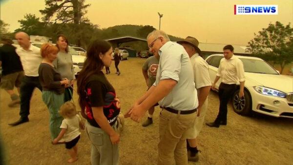 Australia's Prime Minister Scott Morrison attempts to shake a resident's hand