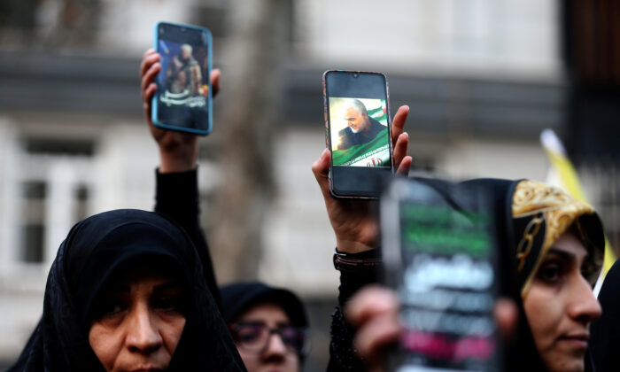 Iranian demonstrators hold up mobile phones showing the picture of the late Iranian General Qassem Soleimani, during a protest against the killing of Soleimani, head of the elite Quds Force, and Iraqi militia commander Abu Mahdi al-Muhandis, who were killed in an air strike at Baghdad airport, in front of United Nations office in Tehran, Iran, on Jan. 3, 2020. (Nazanin Tabatabaee/WANA (West Asia News Agency) via Reuters)