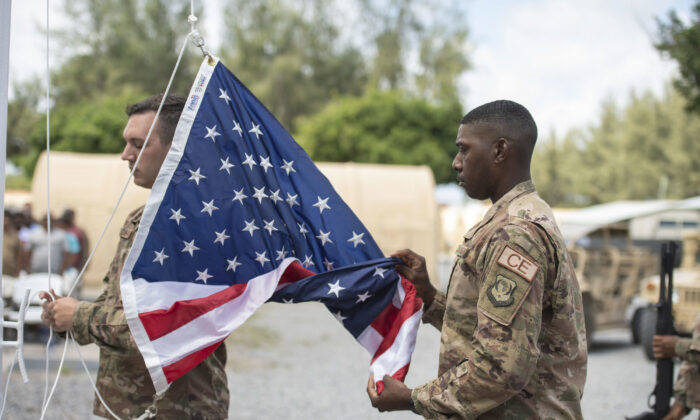 File photo showing U.S. servicemen performing flag detail at Camp Simba, Manda Bay, Kenya, on Aug. 26, 2019. (Staff Sgt. Lexie West/U.S. Air Force via AP)