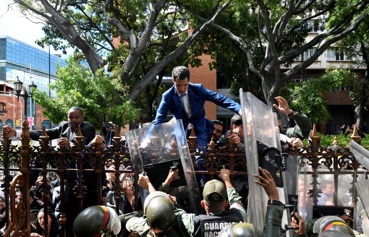 Juan Guaido is helped to climb a railing