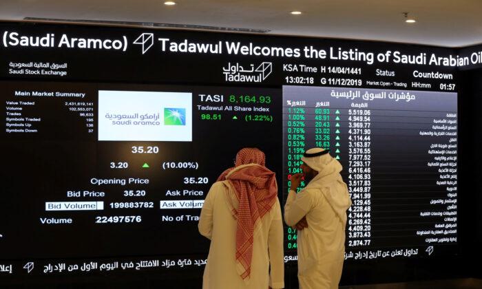 Investors monitor a screen with stock information at the Saudi Stock Exchange (Tadawul) in Riyadh, Saudi Arabia, on Dec. 11, 2019. (Ahmed Yosri/Reuters)