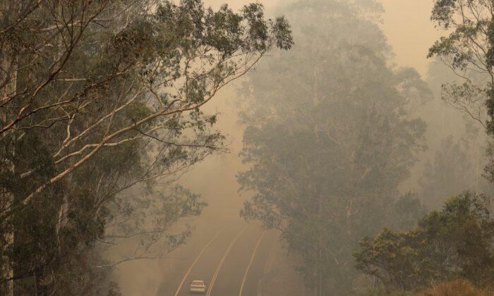 Smoke from wildfires shrouds a road near Moruya, Australia, on Jan. 4, 2020. (Rick Rycroft/AP photo)
