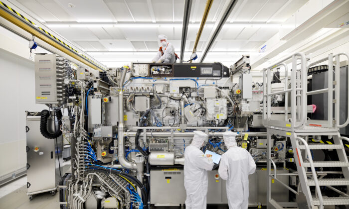 Employees are seen working on the final assembly of ASML's TWINSCAN NXE:3400B semiconductor lithography tool with its panels removed, in Veldhoven, Netherlands, on April 4, 2019. (Bart van Overbeeke Fotografie/ASML/Handout via Reuters)