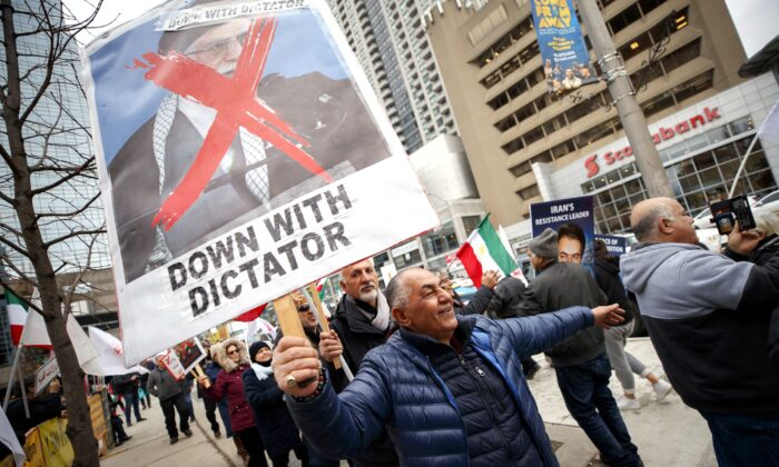 A few dozen Iranian-Canadians gather in Toronto on Jan. 3, 2020, to celebrate the death of Iranian general Gen. Canada is closely monitoring developments after Iraq's parliament called for the expulsion of foreign troops from the country, a spokesman for Defence Minister Harjit Sajjan said. (The Canadian Press/Cole Burston)