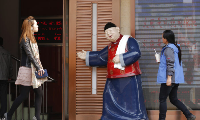 People walk past a statue, placed there to promote a restaurant, at a shopping district in Beijing, China on April 3, 2013. (Kim Kyung-Hoon/Reuters)