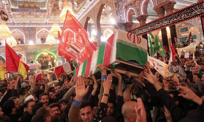 Mourners carry the coffins of slain Iraqi paramilitary chief Abu Mahdi al-Muhandis, Iranian military commander Qasem Soleimani and eight others inside the Shrine of Imam Hussein in the holy Iraqi city of Karbala, Iraq, during a funeral procession on Jan. 4, 2020.  Mohammed Sawaf/AFP via Getty Images