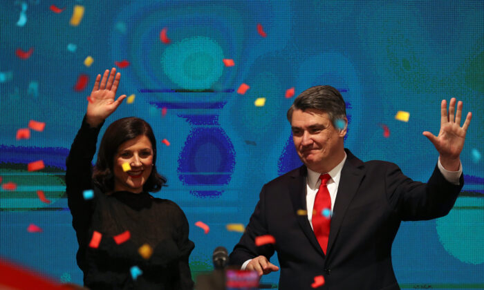 Zoran Milanovic waves next to his wife after first results were announced during the run-off of Croatia's presidential election in Zagreb, Croatia on Jan. 5, 2020. (Marko Djurica/Reuters)