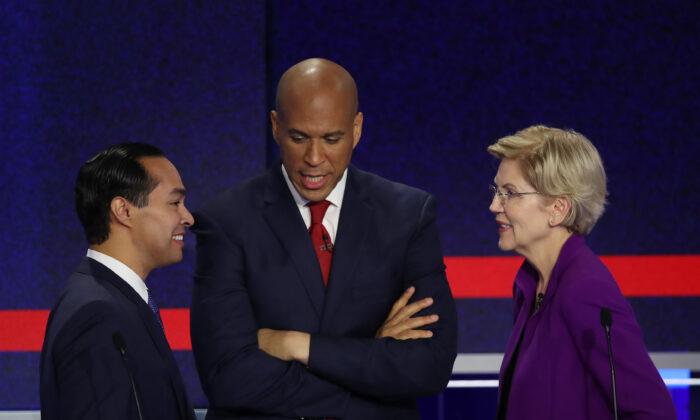 (L-R) Former housing secretary Julian Castro, Sen. Cory Booker (D-N.J.), and Sen. Elizabeth Warren (D-Mass.) talk during the first night of the Democratic presidential debate in Miami, Florida, on June 26, 2019. (Joe Raedle/Getty Images)
