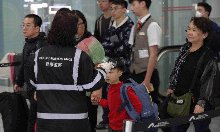 A health surveillance officer uses a device to check temperature of passengers near the immigration counters at the Hong Kong International airport, on Jan. 4, 2020. (AP Photo/Andy Wong)