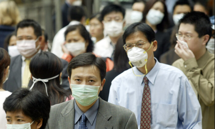 People wear masks on the street to protect against a deadly pneumonia virus in Hong Kong, on March 31, 2003. (Peter Parks/AFP/GettyImages)