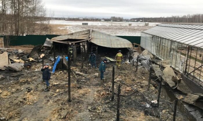 Emergency Situations employees work at the side of the metal construction of a greenhouse farm in Nesterovo, Russia, on Jan. 7, 2020. (Ministry of Emergency Situations press service via AP)