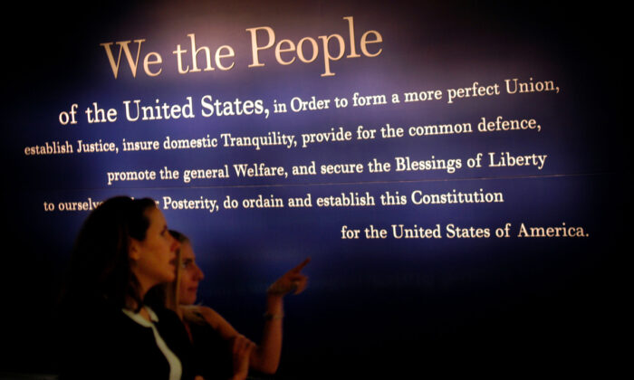 Two women walk past a painting of the beginning of the U.S. Constitution during a preview of the National Constitution Center in Philadelphia, Penn., on July 1, 2003. (William Thomas Cain/Getty Images)