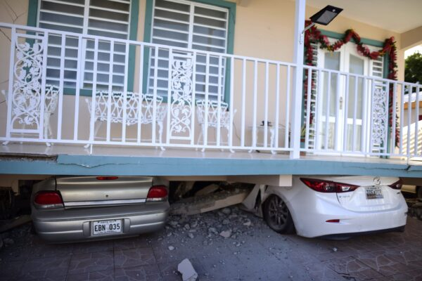 Cars are crushed under a home