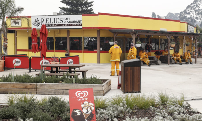 Strike team firefighters gather outside a cafe in Cann River, Australia, on Jan. 6, 2020. Milder weather conditions have provided some relief for firefighters in Victoria as bushfires continue to burn across the East Gippsland area, as clean up operation and evacuations continue. (Darrian Traynor/Getty Images)