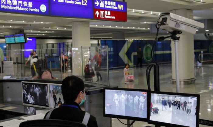 A health surveillance officer monitors passengers arriving at the Hong Kong International Airport in Hong Kong on Jan. 4, 2020. (AP Photo/Andy Wong)