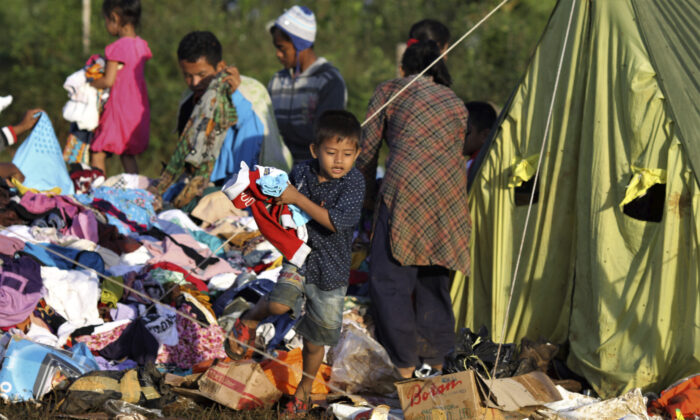 A young boy holds clothings he picked from a pile of relief goods at a temporary shelter for people who are affected by landslide, in Bogor, West Java, Indonesia on Jan. 5, 2020. (Rangga/AP)