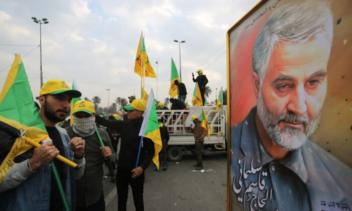 Supporters of the Hashed al-Shaabi paramilitary force and Iraq's Hezbollah brigades pose for a picture next to a poster of Iranian military commander Qasem Soleimani during a funeral, for Soleimani and Iraqi paramilitary chief Abu Mahdi al-Muhandis, both killed by a U.S. airstrike, in Baghdad, Iraq on Jan. 4, 2020. (Ahmad Al-Rubaye/AFP via Getty Images)